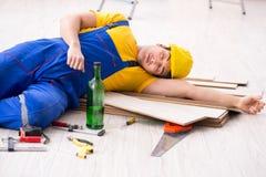 O álcool bebendo do reparador do assoalho durante a ruptura fotos de stock