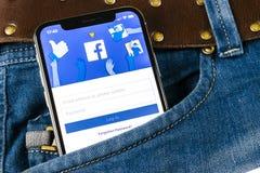 O ícone da aplicação de Facebook no close-up da tela do smartphone do iPhone X de Apple nas calças de brim pocket Ícone de Facebo Foto de Stock