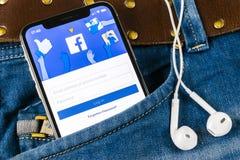 O ícone da aplicação de Facebook no close-up da tela do smartphone do iPhone X de Apple nas calças de brim pocket Ícone de Facebo Imagem de Stock Royalty Free