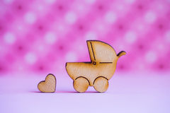 O ícone de madeira do carrinho de bebê e do pouco coração no rosa manchou o backg Fotografia de Stock Royalty Free
