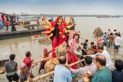 O ídolo de Durga da deusa está sendo imergido no rio santamente Ganges fotos de stock