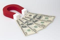 O ímã vermelho atrai notas de banco do dólar. Fotos de Stock Royalty Free