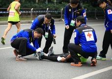 O ò corredor de maratona internacional obteve um ferimento, voluntários que ajudam esticando seus pés Imagens de Stock Royalty Free