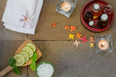 O óleo aromático na bacia de madeira, queimada vela, flores alaranjadas amarelas do rosa, cortou o cal, folha, toalha branca no f Fotos de Stock Royalty Free