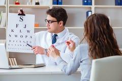 O ótico do doutor com a carta da letra que conduz uma verificação do teste do olho imagens de stock