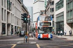 O ônibus de excursão original pintado como Union Jack em uma rua na cidade de Londres, Reino Unido imagem de stock royalty free
