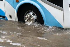 O ônibus espirra através de uma grande poça em uma rua inundada Foto de Stock