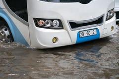O ônibus espirra através de uma grande poça em uma rua inundada Imagem de Stock Royalty Free