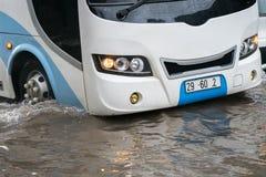 O ônibus espirra através de uma grande poça em uma rua inundada Imagens de Stock