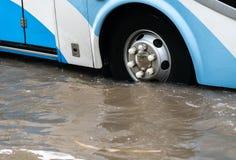 O ônibus espirra através de uma grande poça em uma rua inundada Imagem de Stock