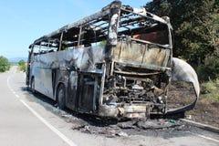 O ônibus queimado é visto na estrada após travado no fogo durante o curso imagens de stock royalty free