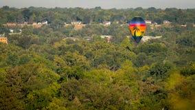 O único balão de ar quente flutua sobre a cidade das árvores sobre um blan Imagem de Stock