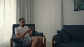 O único homem está aproximando-se para apresentar e está tomando-se o móbil, sentando-se na cadeira e para relaxar vídeos de arquivo