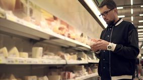 O único homem está tomando pacotes com queijo e carne em um supermercado e em uma colocação vídeos de arquivo