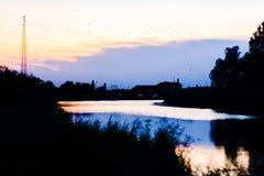 o ένας ποταμός στην ανατολή, αυτό απεικονίζει τα χρώματα του ουρανού ενώ όλα γύρω από τον γίνονται σκοτεινά στοκ φωτογραφία