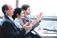 o επιχειρησιακή ομάδα που επιδοκιμάζει τον ομιλητή, που κάθεται στον εργασιακό χώρο στοκ εικόνες με δικαίωμα ελεύθερης χρήσης
