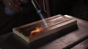 o Ο ξυλουργός καίει τις επιτροπές με έναν καυστήρα αερίου για το μαύρισμα φιλμ μικρού μήκους