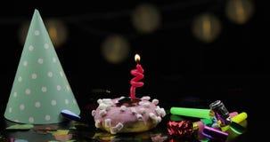 o Розовый донут и красная праздничная свеча на ей Золотое падение confetti акции видеоматериалы