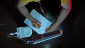 o 一件黄色T恤杉的一个人工作在黑暗的一张桌上 一个人在纸用手写 股票录像