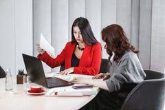 o 两位女孩设计师与膝上型计算机和文献一起使用在坐在的项目 免版税图库摄影