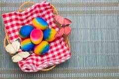 o 五颜六色的复活节彩蛋顶视图在一个篮子的在一张绿色竹席子的红色方格的餐巾 空间为 免版税库存图片