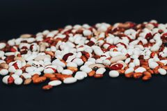 o 在黑背景驱散的多彩多姿的豆 与空间的背景文本的 图库摄影