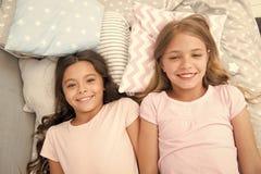 o 女孩孩子在床放置有逗人喜爱的枕头顶视图 睡衣派对概念 获得的女孩乐趣 免版税图库摄影