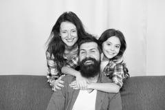 o 家庭一起度过周末 获得友好的家庭乐趣一起 放松在长沙发的妈妈爸爸和女儿 库存图片