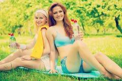 佩带体育的两位美丽的白种人女性给坐的o穿衣 库存图片
