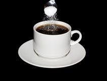 O açúcar é derramado de uma colher em uma xícara de café Imagens de Stock Royalty Free