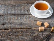 O açúcar de bastão marrom branco do copo e dos pires de chá em um fundo de madeira rústico copia o espaço Foto de Stock
