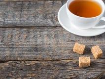 O açúcar de bastão marrom branco do copo e dos pires de chá em um fundo de madeira rústico copia o espaço Imagens de Stock Royalty Free