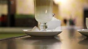 O açúcar de protuberância é posto sobre os pires perto do copo com os tenazes de brasa vídeos de arquivo