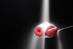 O açúcar derrama na colher com framboesas fotos de stock royalty free