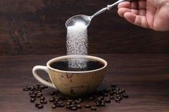 O a??car derrama no copo de Coffe com feij?es de Coffe fotos de stock