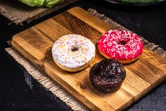 O açúcar revestiu anéis de espuma e mentira do queque em uma placa de madeira fotografia de stock