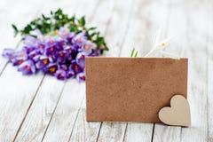 O açafrão bonito floresce em uma cesta perto do cartão vazio para seu texto no fundo de madeira Fotografia de Stock Royalty Free