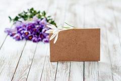 O açafrão bonito floresce em uma cesta perto do cartão vazio para seu texto no fundo de madeira Imagem de Stock