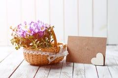O açafrão bonito floresce em uma cesta perto do cartão vazio para seu texto no fundo de madeira toned Imagens de Stock