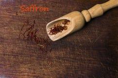 O açafrão rosqueia com a pá da especiaria no fundo de madeira, close up, Fotografia de Stock Royalty Free