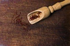 O açafrão rosqueia com a pá da especiaria no fundo de madeira, close up, Fotos de Stock