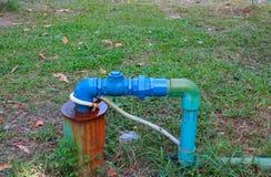 O aço do encanamento da válvula da água manda as tubulações do reparo com alterar do azul juntado e pintado na grama foto de stock royalty free