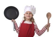 6 o 7 años de la niña en cocinar el sombrero y el delantal rojo que juegan la cacerola y la cuchara que se sostienen felices sonr Foto de archivo libre de regalías