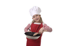 6 o 7 años de la niña en cocinar el sombrero y el delantal rojo que juegan la cacerola y la cuchara que se sostienen felices sonr Fotografía de archivo