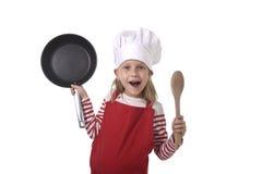 6 o 7 años de la niña en cocinar el sombrero y el playin rojo del delantal Imagenes de archivo