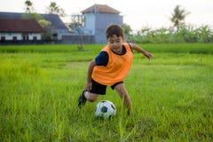 8 o 9 años felices y niño emocionado que juega a fútbol al aire libre en el chaleco del entrenamiento del jardín que lleva que co imagen de archivo