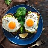 O abacate saudável do café da manhã brinda a tabela saudável alegre da opinião superior das caras do ovo frito imagem de stock