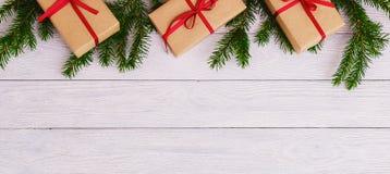 O abeto decorativo do verde do fundo do Natal ramifica fundo de madeira dos presentes Imagem de Stock