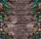 O abeto do Natal ramifica com luzes e as decorações vermelhas no fundo de madeira Composição do Xmas e do ano novo feliz fotografia de stock