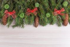 O abeto dos feriados de inverno da decoração ramifica com os cones com as nuvens verdes dos galhos e da curva vermelha Imagem de Stock Royalty Free